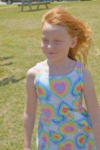 Gabby 7 3/4 years old, wearing FabKids Rainbow Heart Skater Dress-size 8