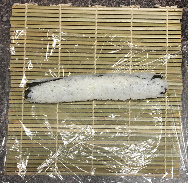 Once the Caterpillar Roll is fully rolled, give the whole thing a hug with your fingers. This will compress the rice which will help keep it from falling apart when you slice